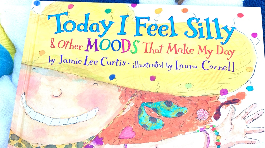 Cover of Today I Feel Silly.  A giant grinning face takes up most of the cover.  The girl has curly red hair full of bows and wears a wide-brimmed yellow hat.  She's waving one arm, which has two multicolored bracelets.